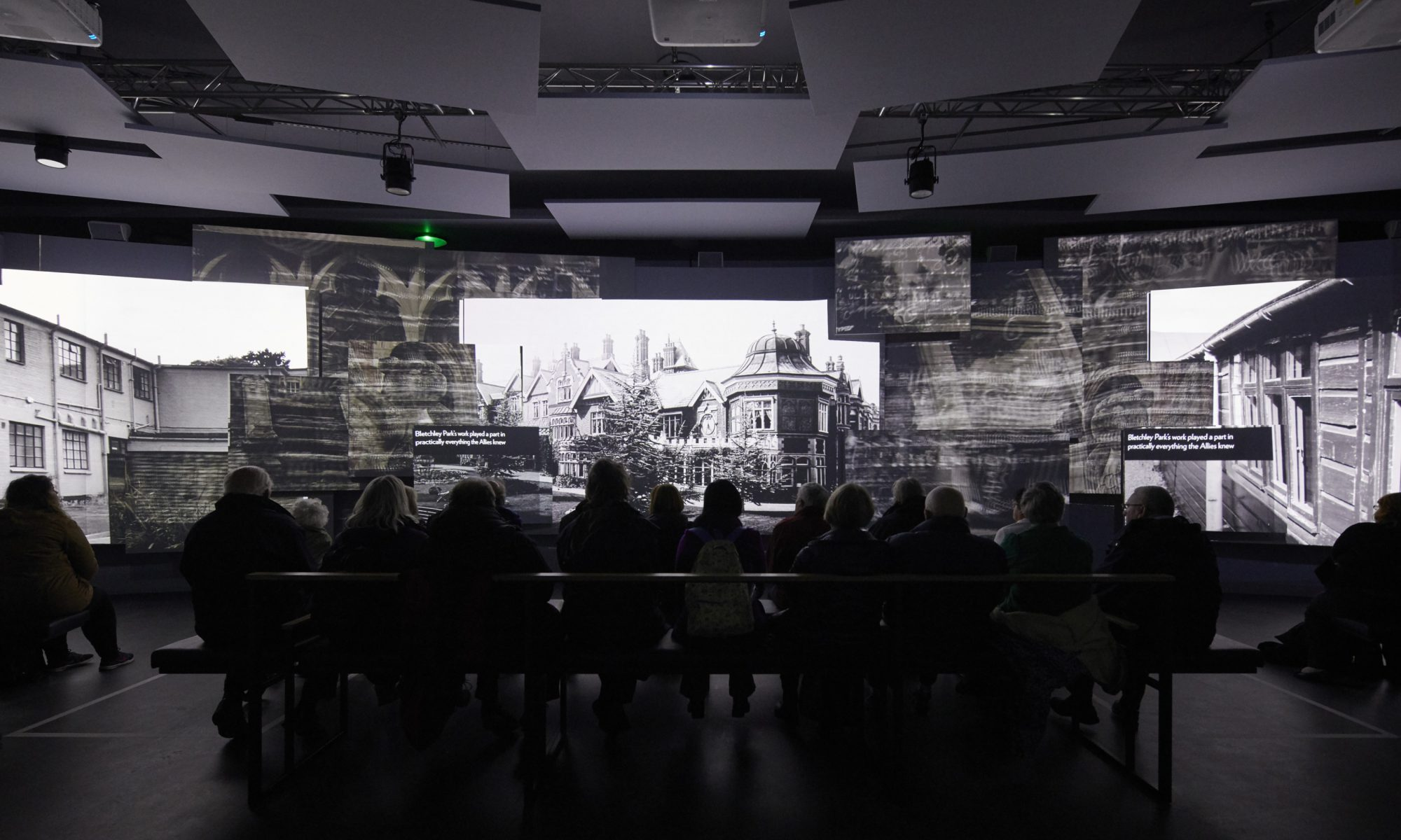 A group of people watch an animated display on the history of Bletchley Park and its role in WW2.