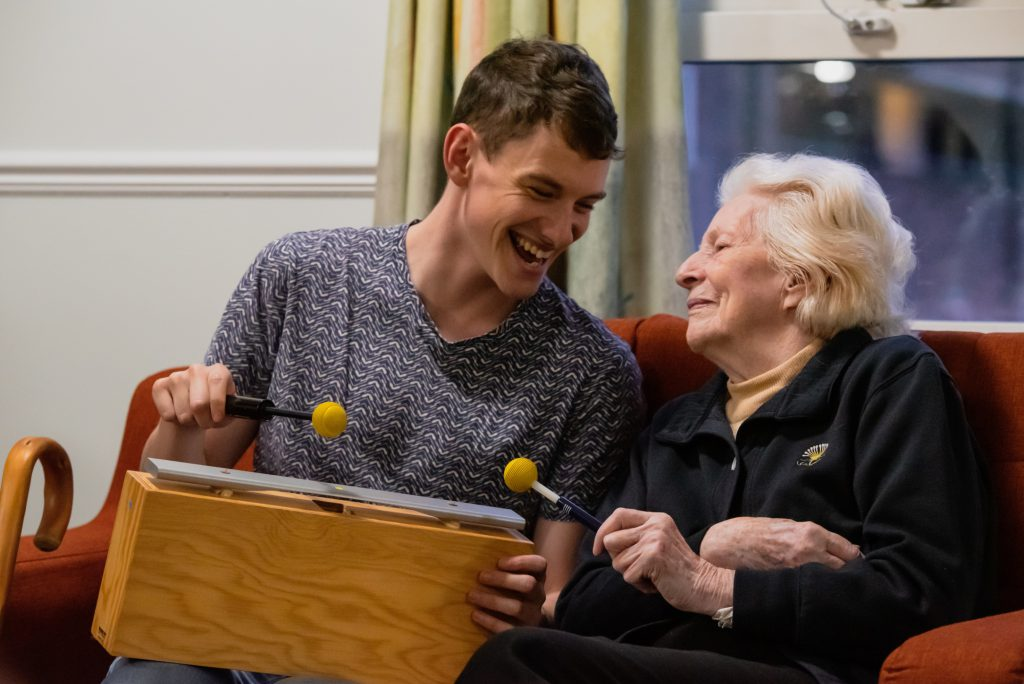 A volunteer supports an older person during a music lesson at Wigmore Hall